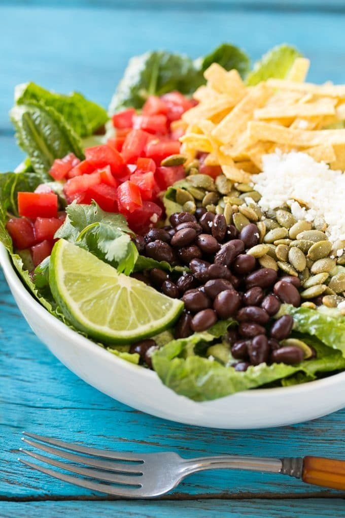Mexican Caesar salad with black beans, tomatoes, cotija cheese and tortilla strips.