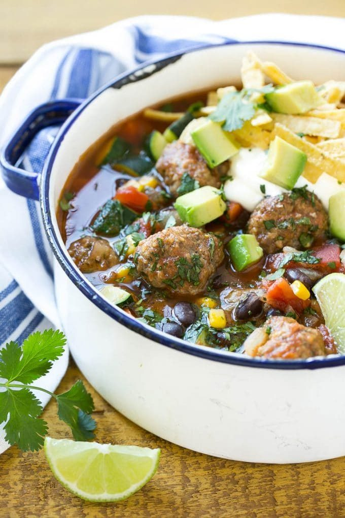 A pot of Mexican meatball soup topped with sour cream, tortilla strips and avocado.