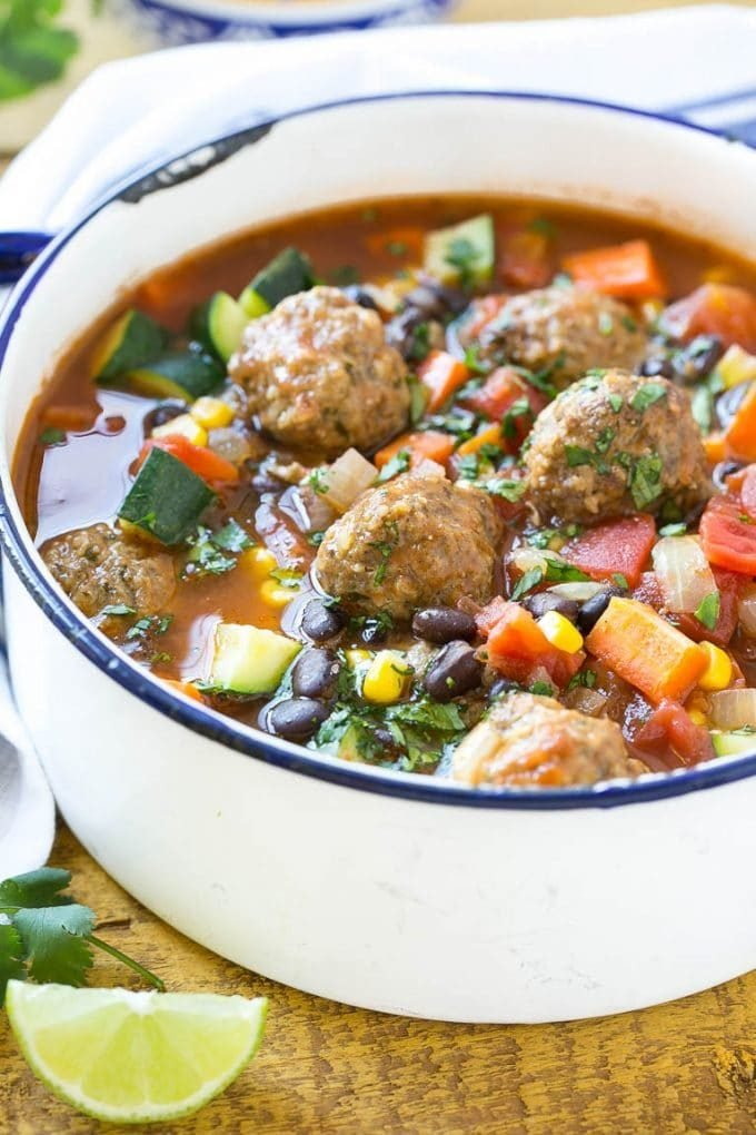 A pot of Mexican meatball soup with vegetables and black beans.