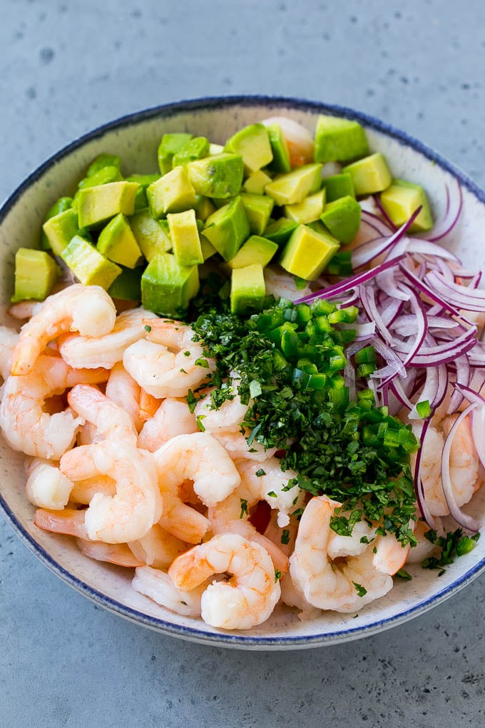 Shrimp, red onion, avocado, jalapeno and cilantro in a serving bowl.