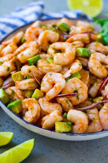 A serving bowl of Mexican shrimp cocktail which contains small shrimp, diced avocado, herbs and jalapeno.