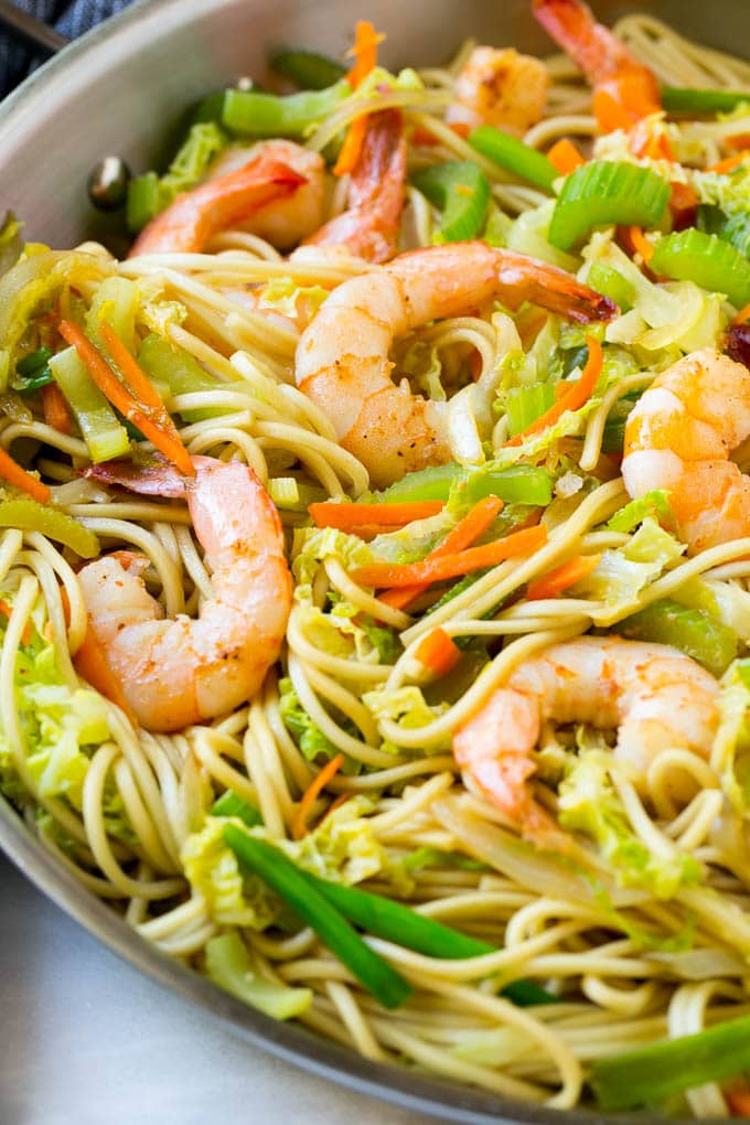 Shrimp nestled in a pan of chow mein noodles with colorful vegetables.