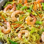 A pan of shrimp chow mein noodles with vegetables.