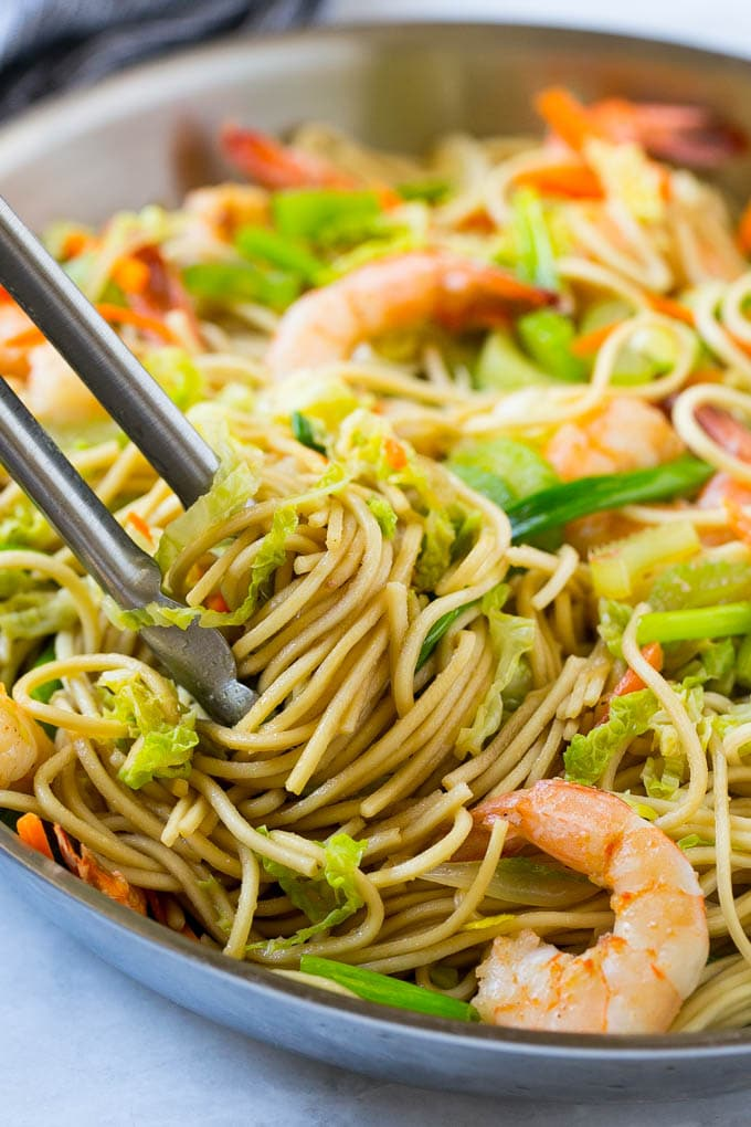 A pan filled with shrimp chow mein with a pair of tongs lifting out the noodles.