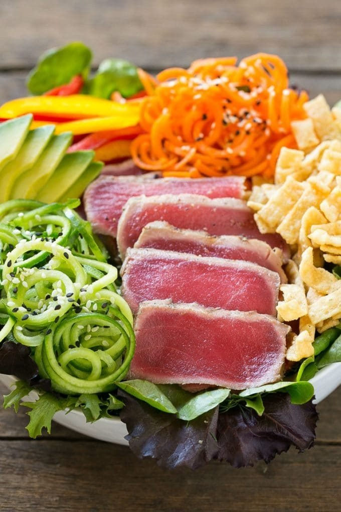 A bowl of ahi tuna salad with thinly sliced seared tuna and an assortment of colorful veggies.