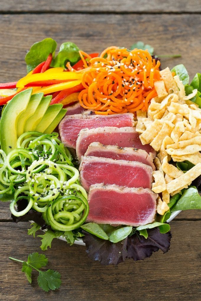 A bed of greens with seared tuna, carrots, cucumber and wonton strips.