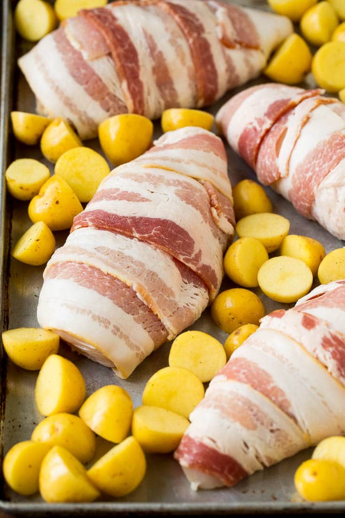 Bacon wrapped chicken with potatoes on a sheet pan.