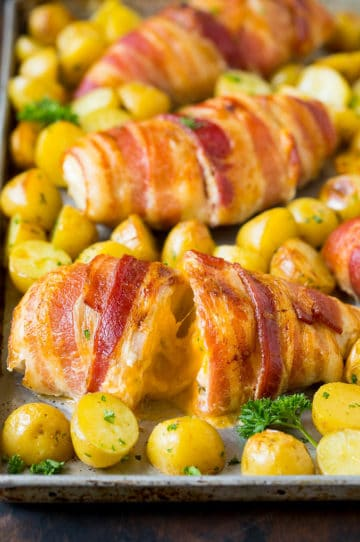 Bacon wrapped stuffed chicken breast on a sheet pan with roasted potatoes.