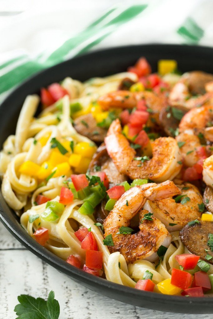 This recipe for Cajun shrimp and sausage pasta is sauteed shrimp and smoked sausage with colorful vegetables, all served over a creamy fettuccine pasta. Dinner's ready in less than 30 minutes with plenty of bold flavors!