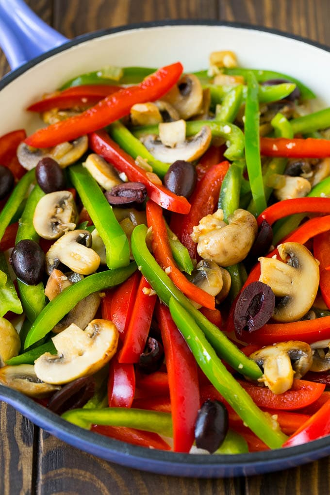 Peppers, mushrooms and olives in a pan.