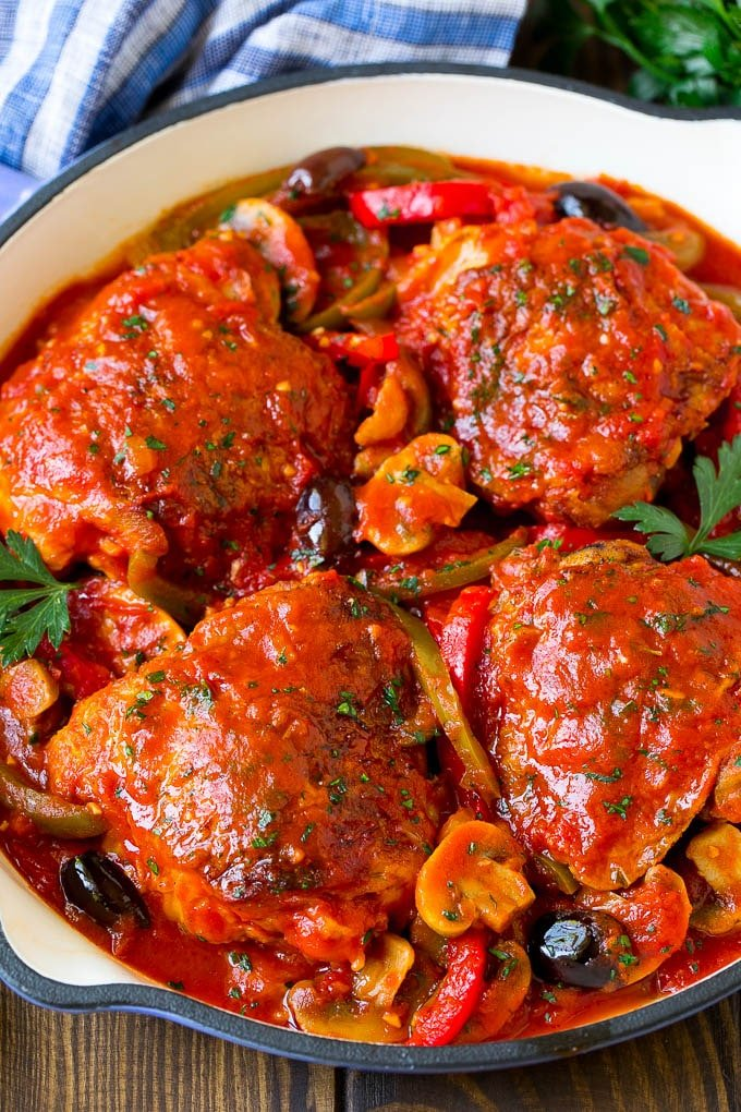 Chicken cacciatore with chicken thighs, peppers, olives and mushrooms in tomato sauce.