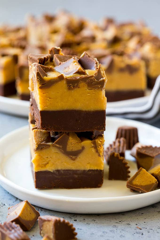 Stacked pieces of chocolate peanut butter fudge on a plate.