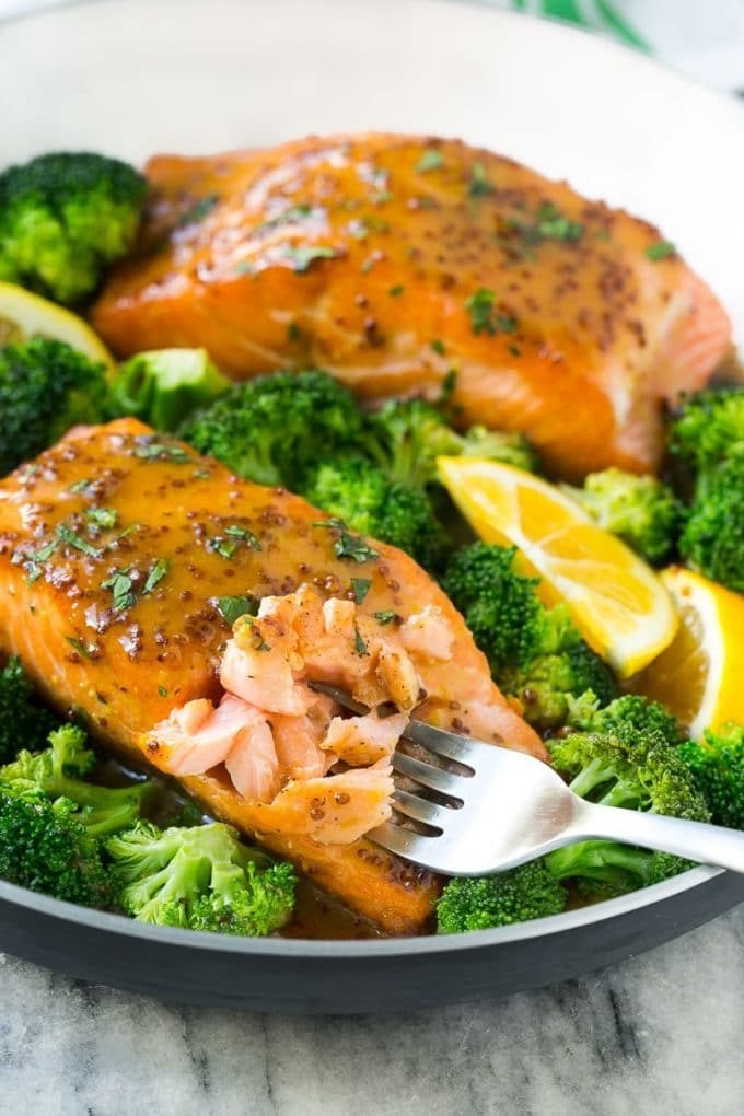 A pan of honey mustard salmon with broccoli and a fork cutting into the fish.