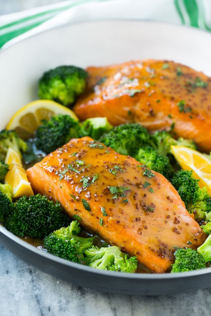 A pan of honey mustard salmon fillets surrounded by broccoli florets.