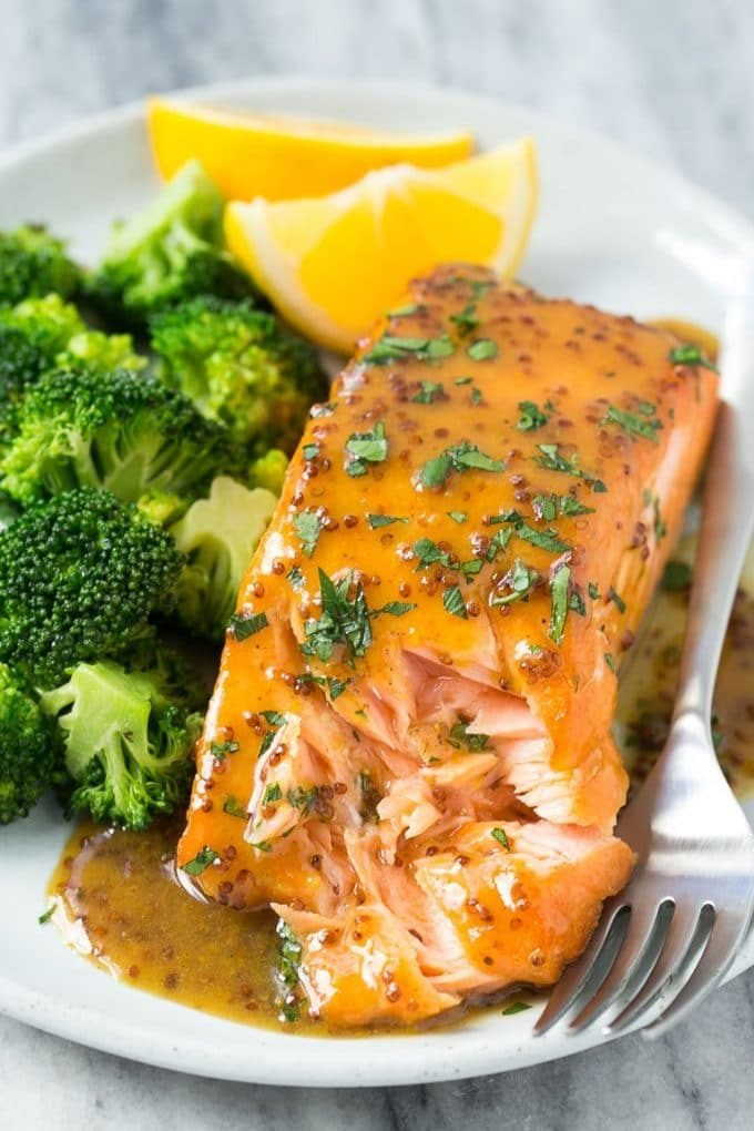 A plate with a honey mustard salmon fillet and cooked broccoli.