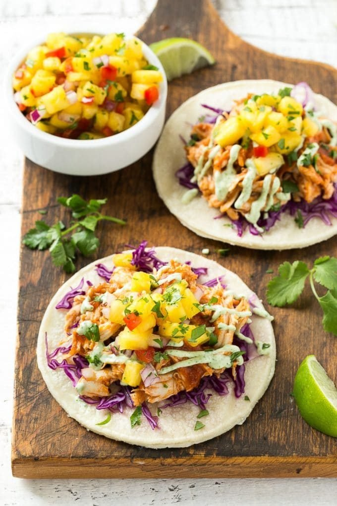 Mini corn tortillas topped with purple cabbage and pulled chicken.