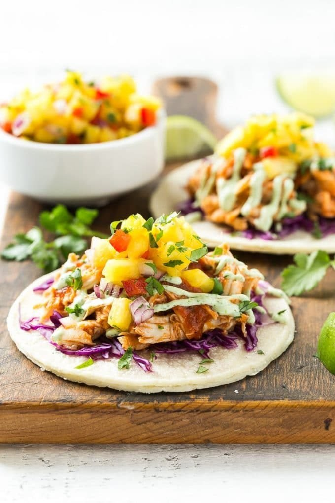 A tortilla topped with cabbage, pulled chicken and pineapple salsa.