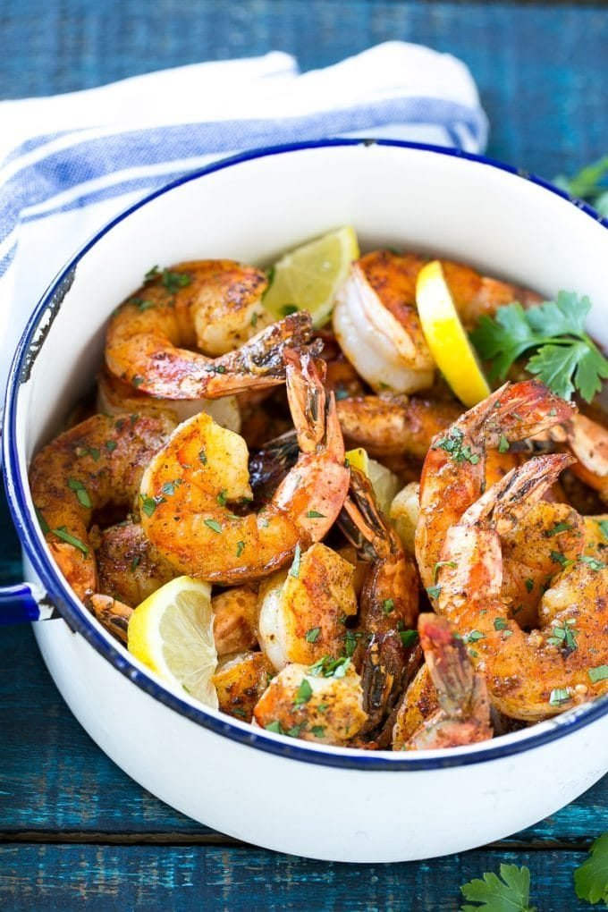 Giant shrimp cooked in a spiced butter sauce, then garnished with lemon slices and chopped parsley.