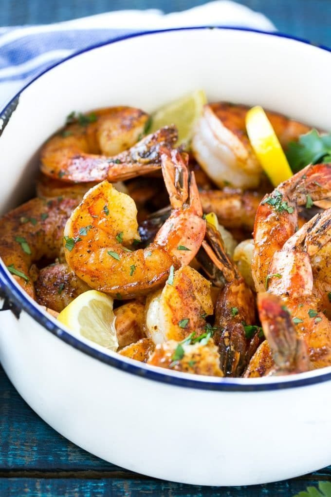 A pot of New Orleans BBQ shrimp garnished with lemon wedges and parsley.