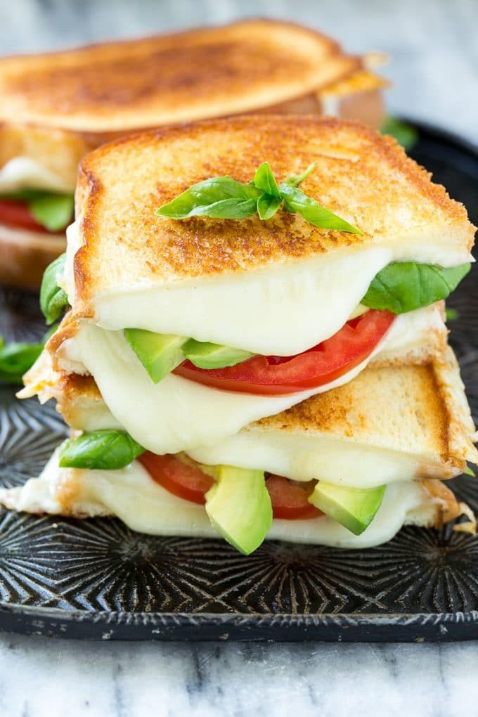 A caprese sandwich with toasted bread, tomatoes, mozzarella cheese, basil and avocado.