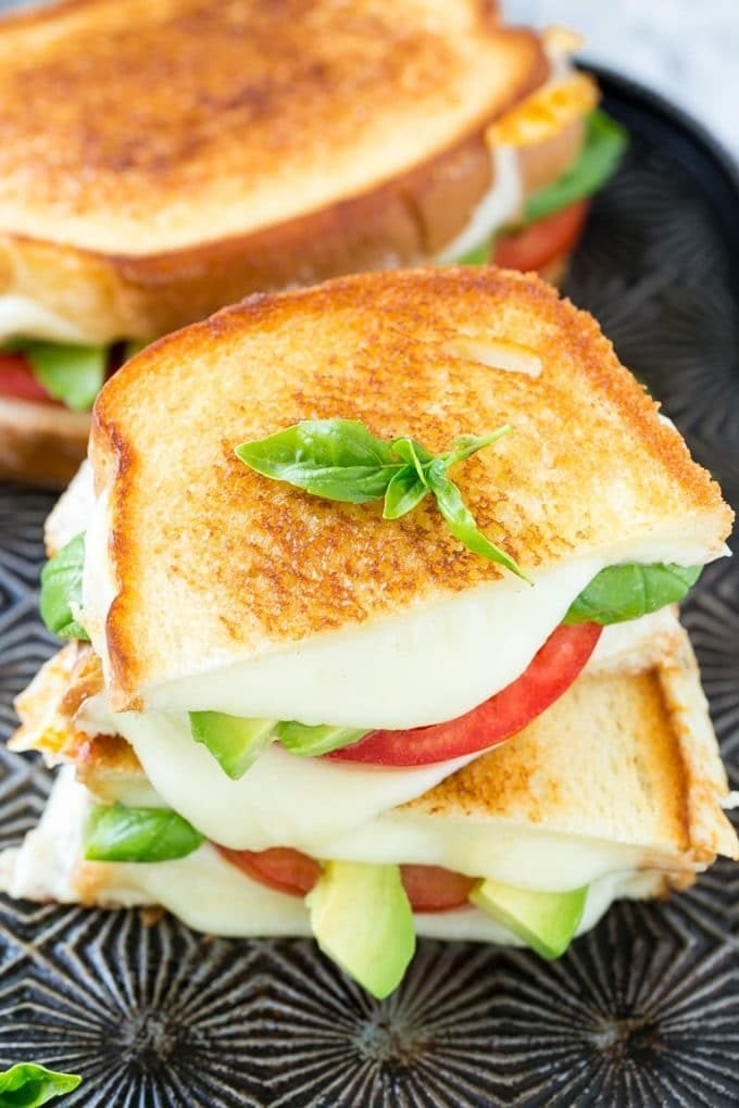 A grilled caprese sandwich with tomato slices, melted cheese and avocado.