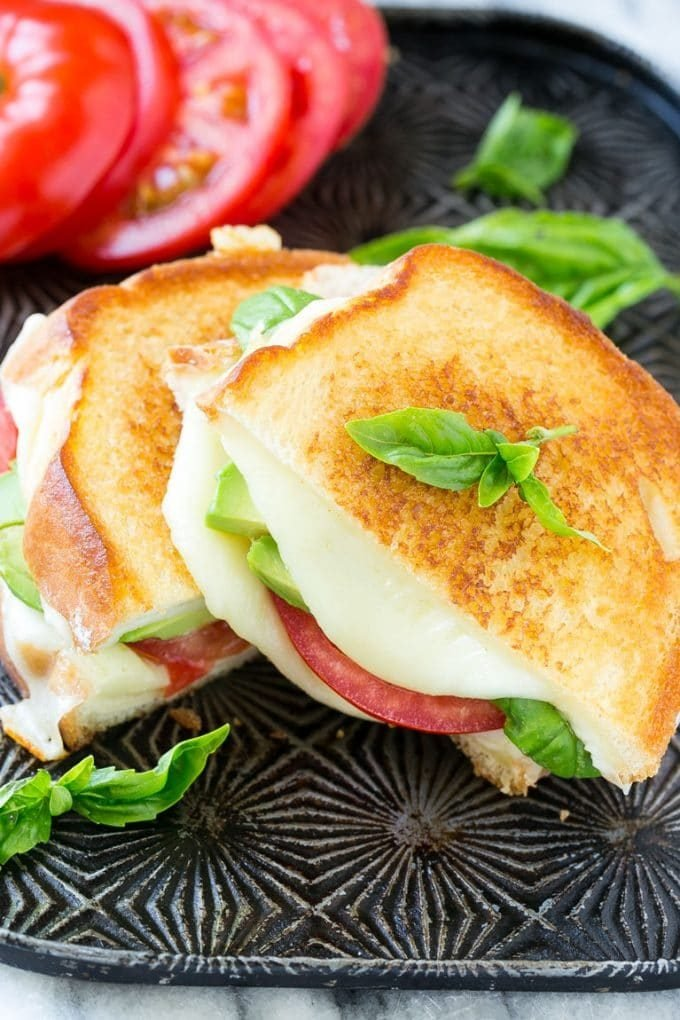 Caprese sandwich with melted mozzarella cheese, fresh tomatoes, sliced avocado and basil leaves.
