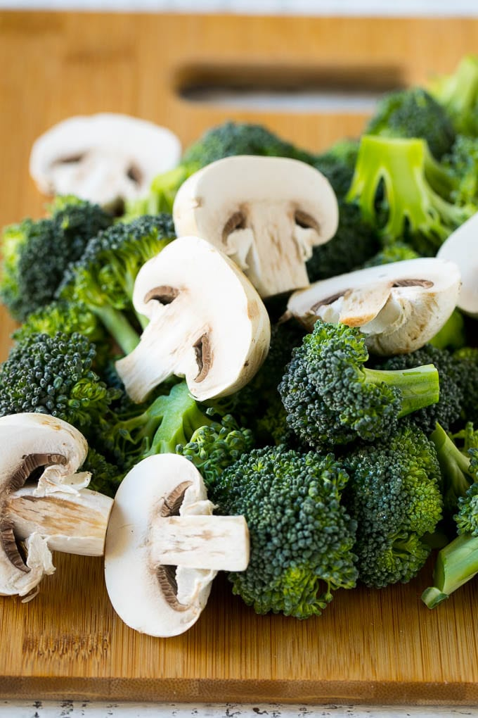Broccoli florets and sliced mushrooms on a cutting board.