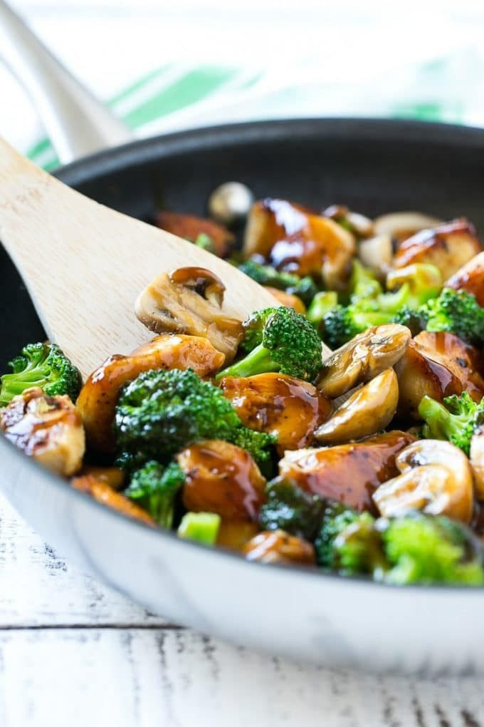 A skillet of chicken and broccoli stir fry with a spatula in it.