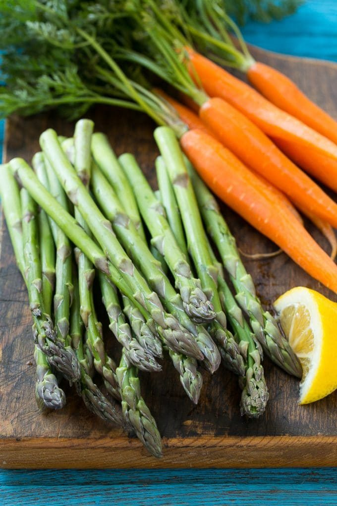 Fresh asparagus and carrots on a cutting board.
