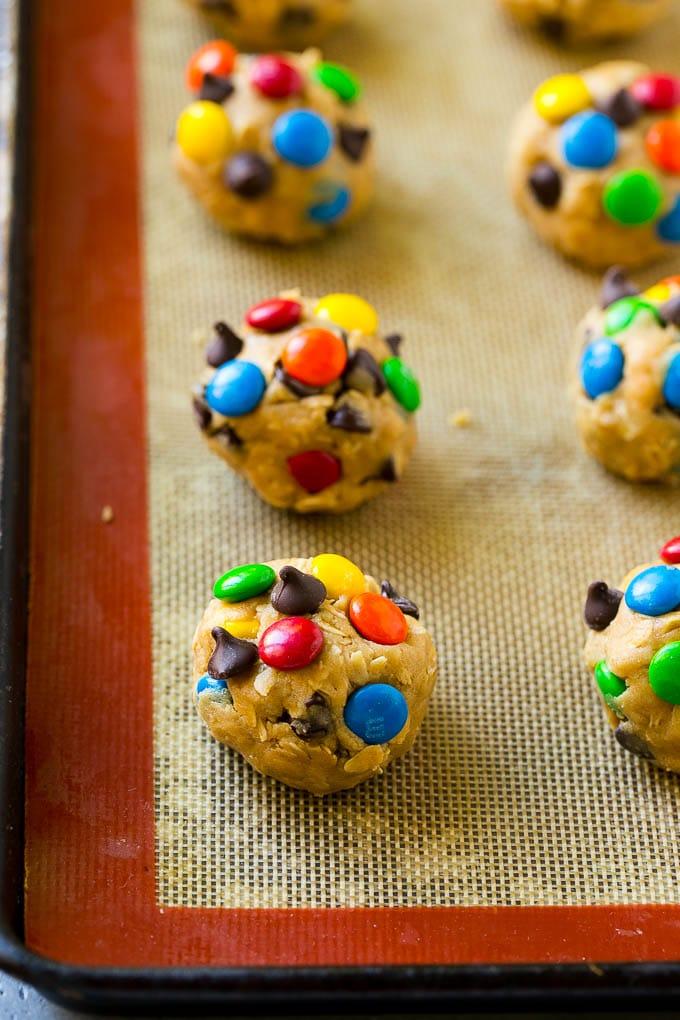 Balls of monster cookie dough on a baking sheet.