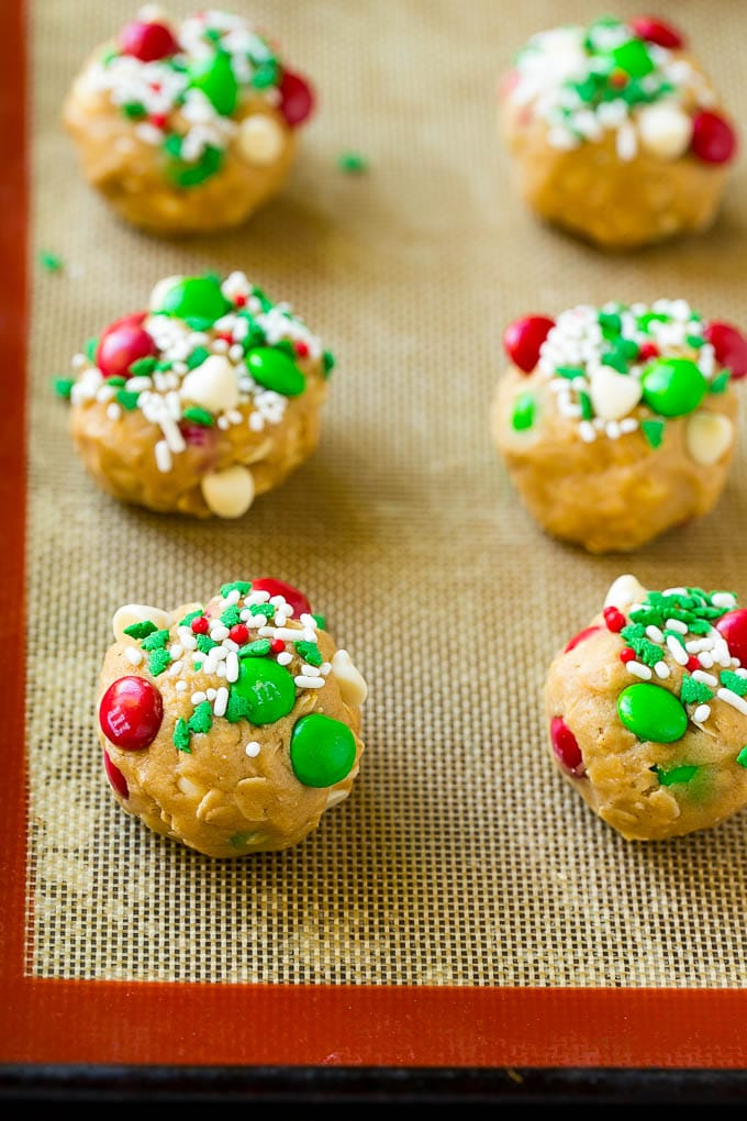 Balls of Christmas monster cookie dough on a baking sheet.