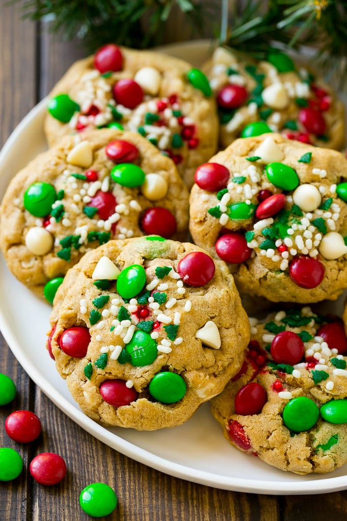 A plate of Christmas monster cookies which are decorated with M&M's, white chocolate and sprinkles.