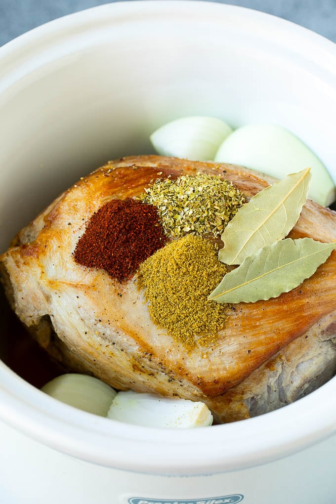 Pork roast with spices and onions in a slow cooker.