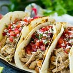 Pork tacos in flour tortillas topped with pico de gallo.
