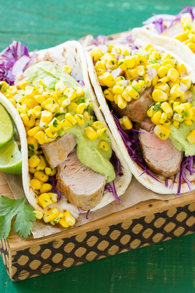 This recipe for pork tenderloin tacos is thinly sliced seasoned pork, layered with cabbage, corn salsa and creamy avocado sauce, all tucked inside warm flour tortillas. A unique take on taco night!