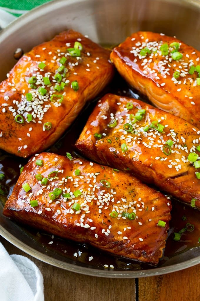 Salmon teriyaki fillets topped with sesame seeds and green onions.