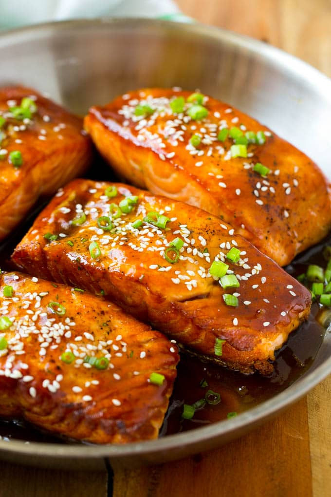 A pan full of teriyaki salmon fillets topped with sesame seeds.