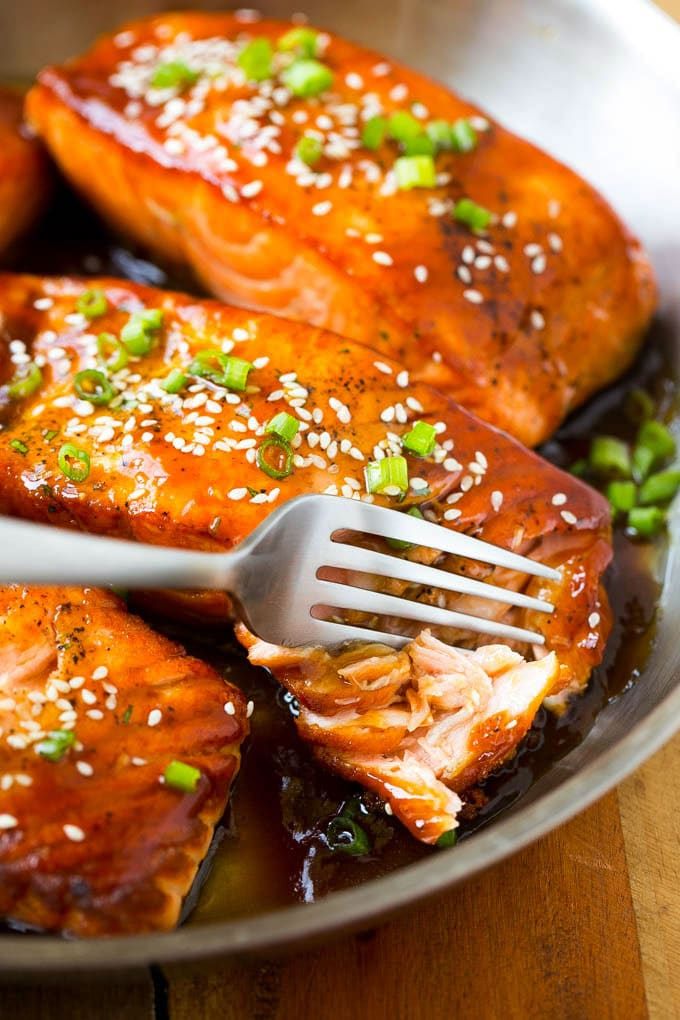 A fillet of teriyaki salmon with a fork cutting into it.