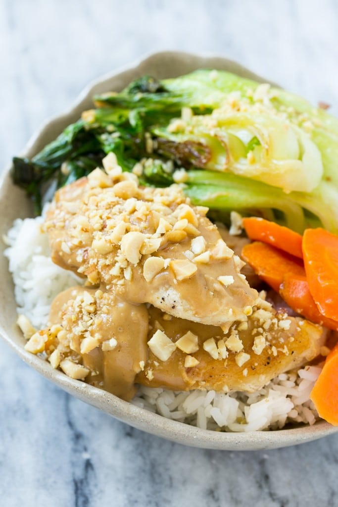 A bowl of Thai peanut chicken and vegetables served over steamed rice.