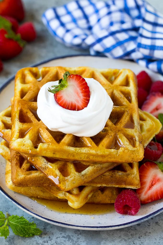 A stack of buttermilk waffles topped with syrup, whipped cream and fresh fruit.