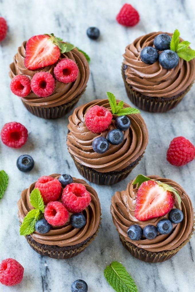 Chocolate hazelnut cupcakes topped with berries and mint sprigs.
