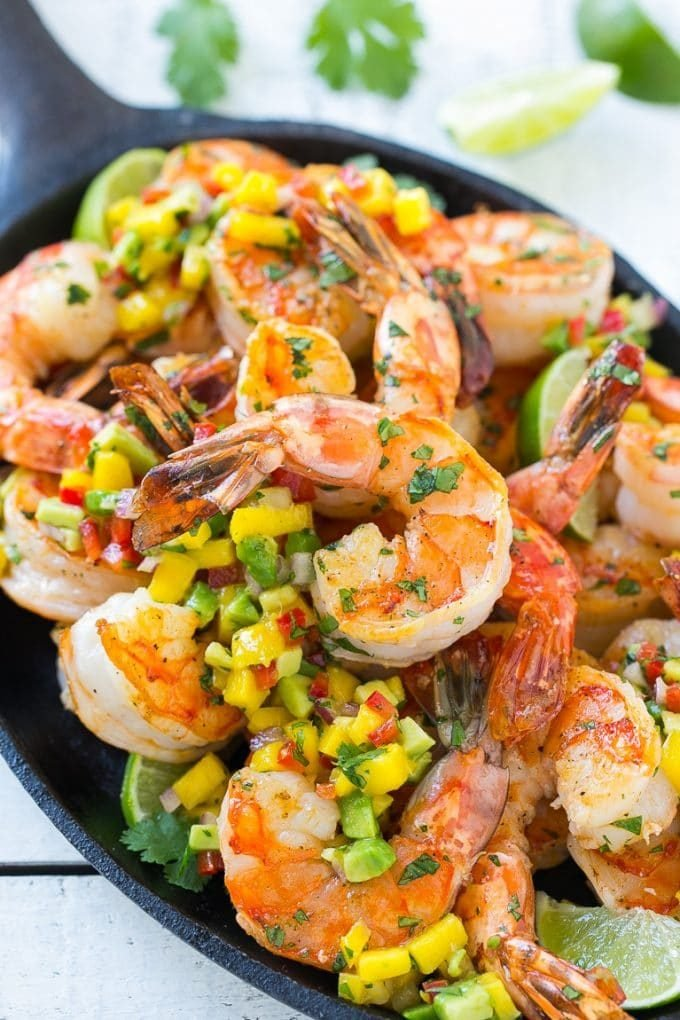 Cilantro lime shrimp on a skillet, topped with mango and avocado salsa.