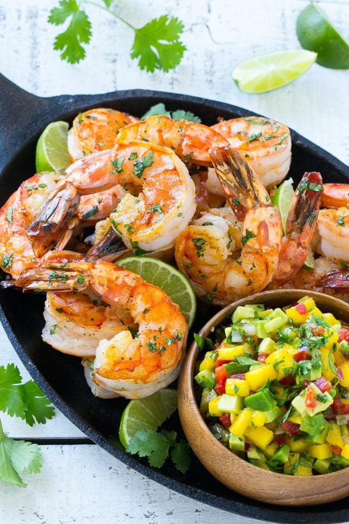 A pan of seared cilantro lime shrimp with a fruit salsa topping.