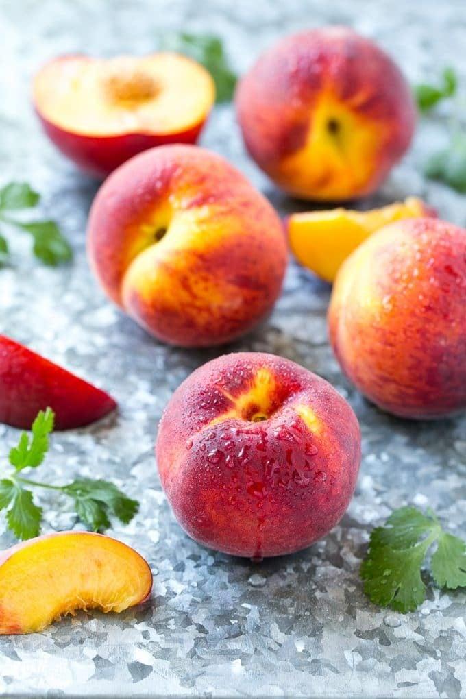 Fresh whole and cut peaches.