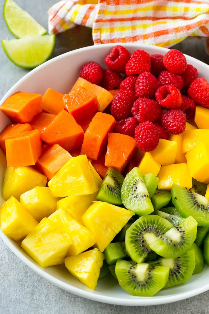 Pineapple, mango, kiwi, papaya and raspberries in a serving bowl.