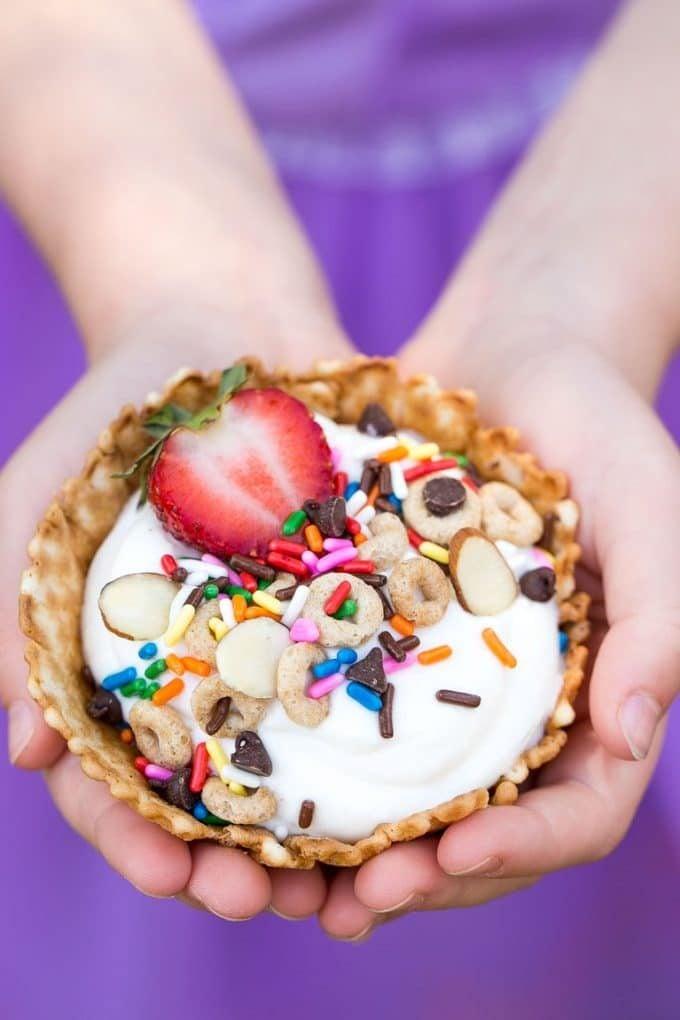 Children's hands holding a breakfast sundae.