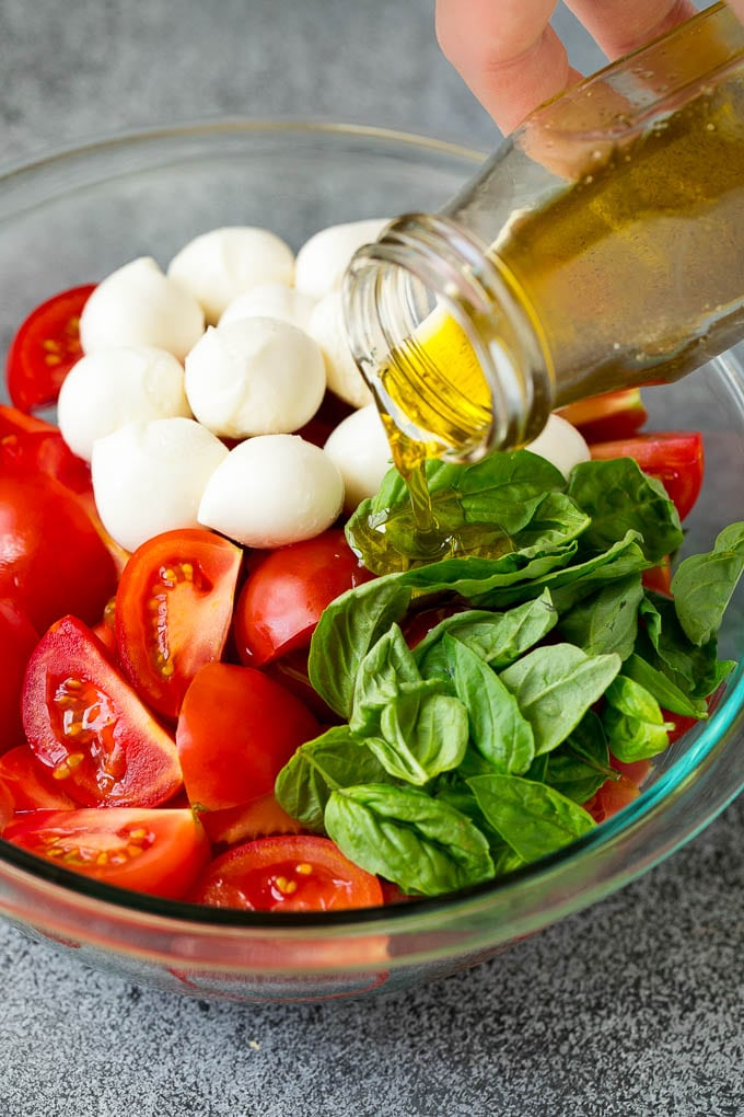 Olive oil being poured over tomatoes, mozzarella and basil leaves.
