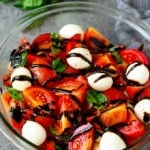 Caprese salad with tomatoes, fresh mozzarella, basil leaves and balsamic glaze.