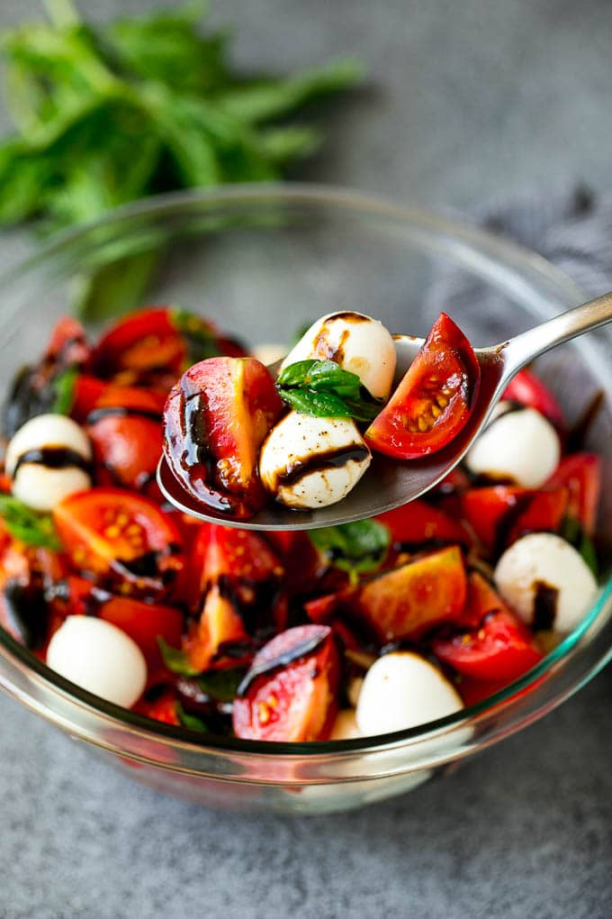 A serving spoon of caprese salad with tomato, mozzarella and basil.