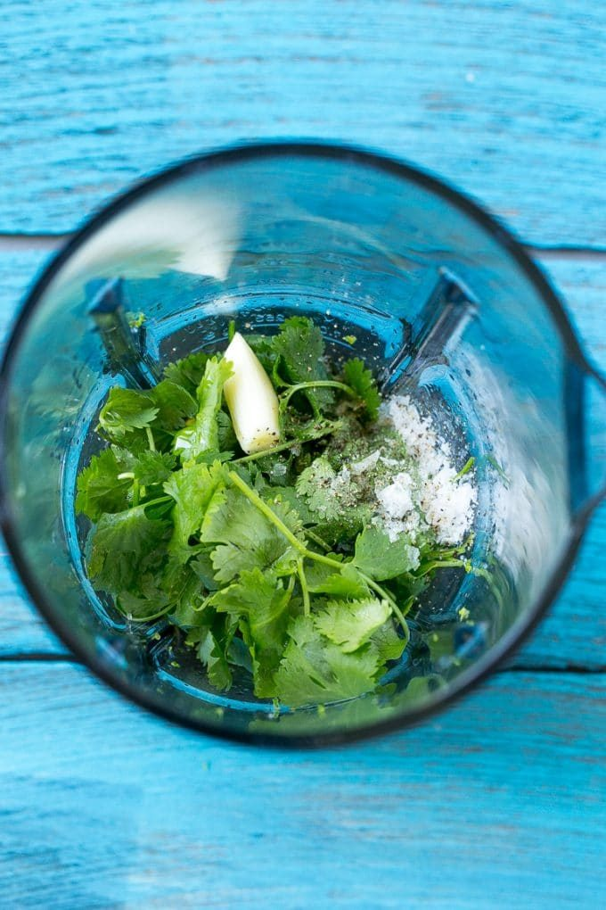 A blender full of cilantro leaves, garlic, lime juice and olive oil.
